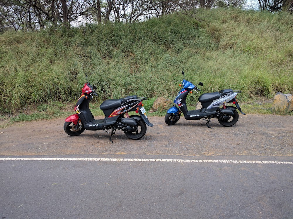 Picture of two Kymco Maui scooter rental mopeds parked on the side of the road